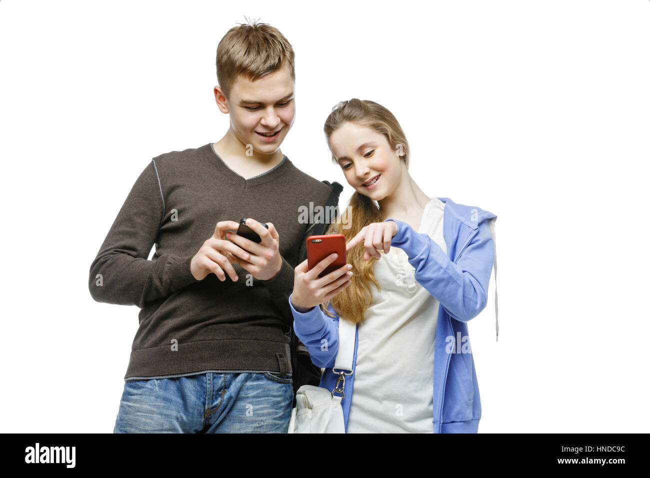 Beautiful teen age boy and girl in casual clothes holding mobile phones. School children texting using cellulars. - Stock Image