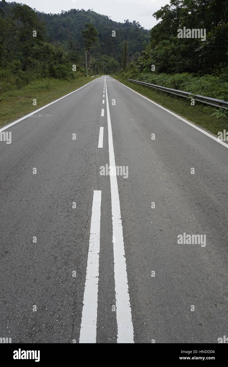 long stretch of empty road with divider lines - Stock Image