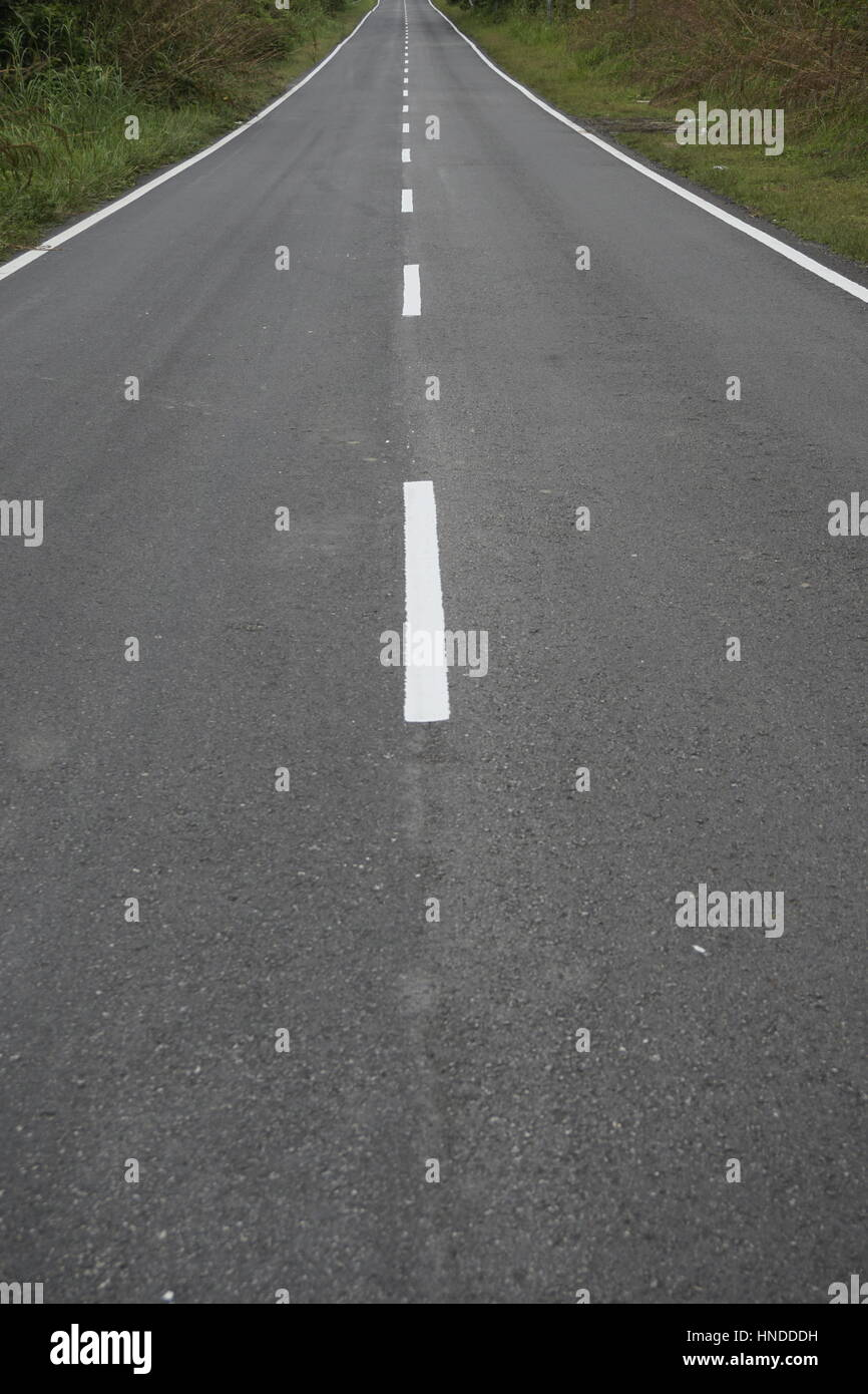 long stretch of empty road with divider lines, focused near the mid-section - Stock Image