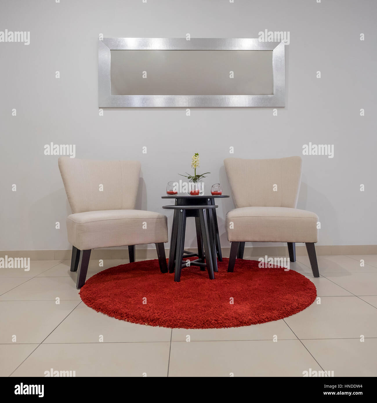 Two Chairs Stand On A Round Red Carpet Mat Above A Mirror And A Small Table  With Decoration