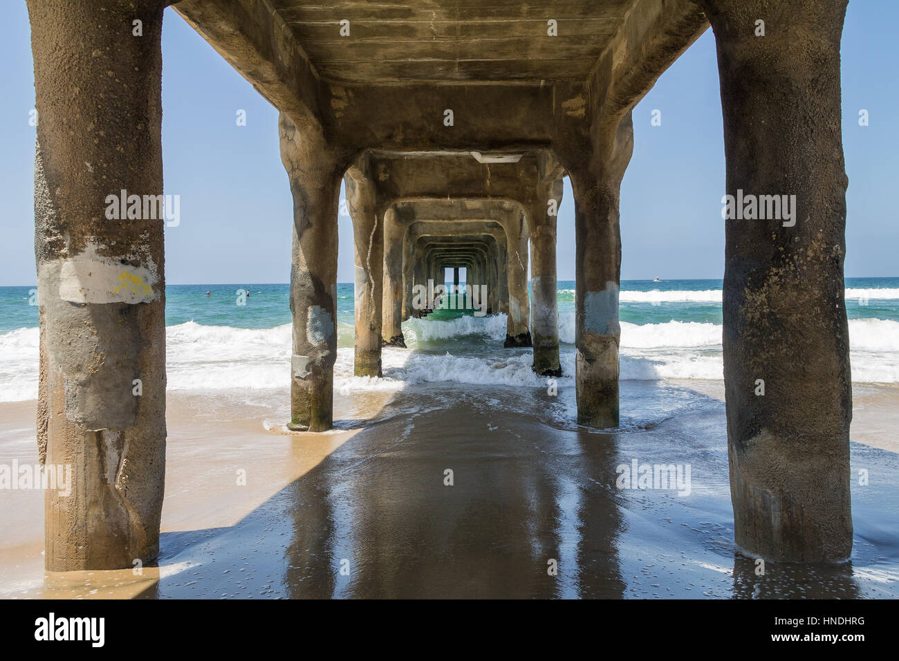 Standing beneath Manhattan Beach Piere as waves crash from the Pacific Ocean - Stock Image