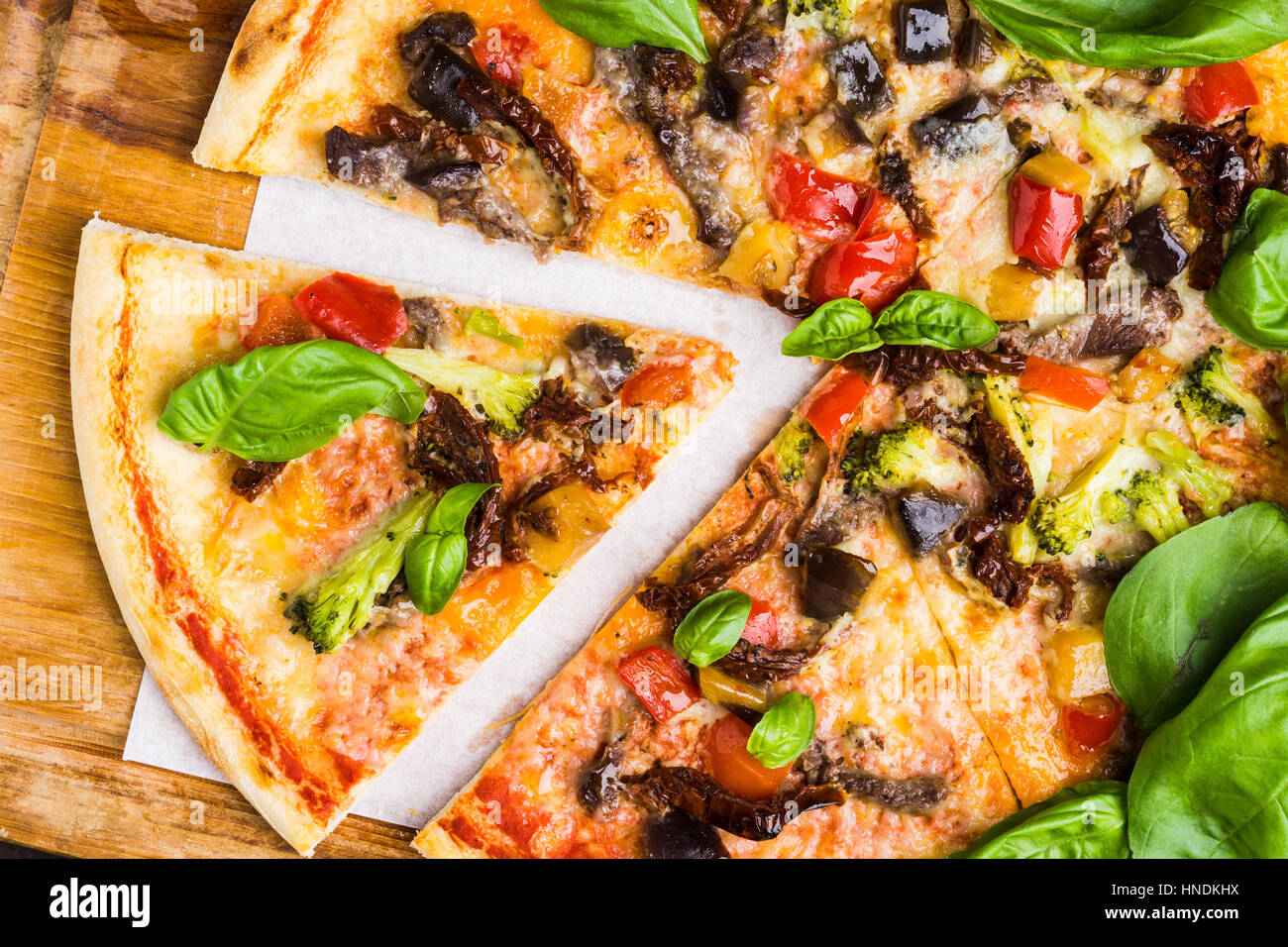 Fresh pizza served on wooden table. Shallow depth of field. - Stock Image