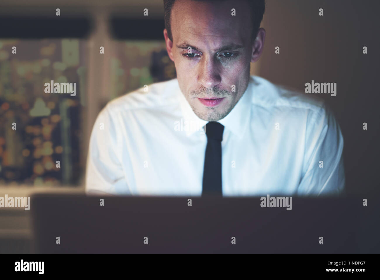 Close up of businessman working overtime on computer, late night work - Stock Image