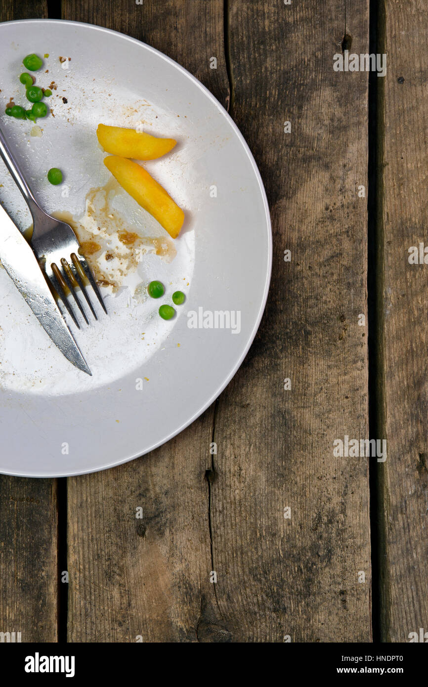 Overhead view of leftovers on a plate with knife and fork on a rustic wooden background Stock Photo