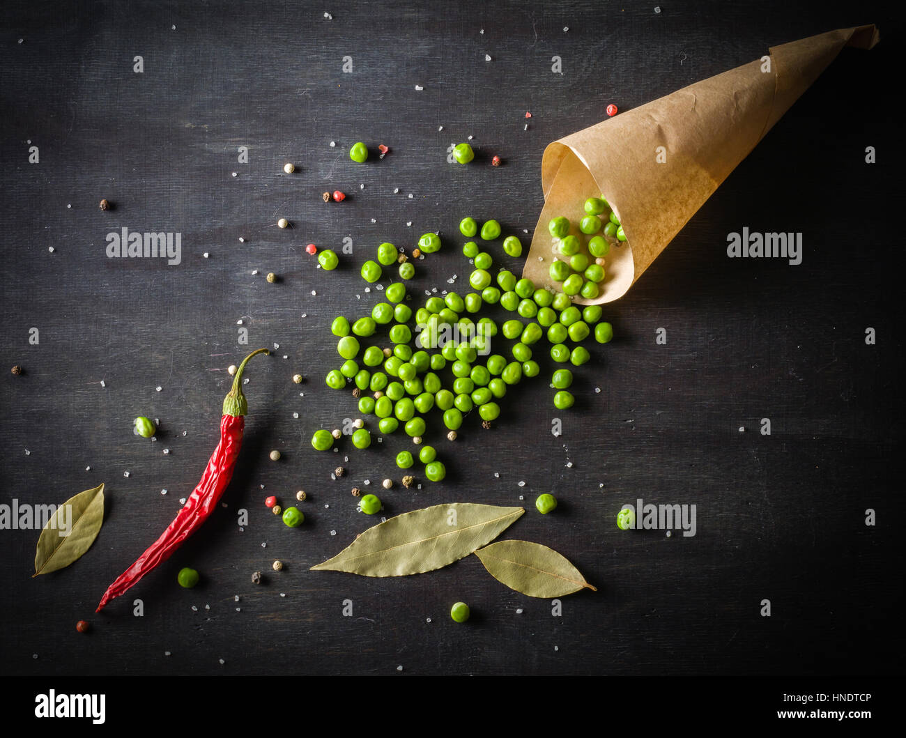 Green peas in a paper bag and chili peppers on a dark wooden background. Top view, space for text - Stock Image