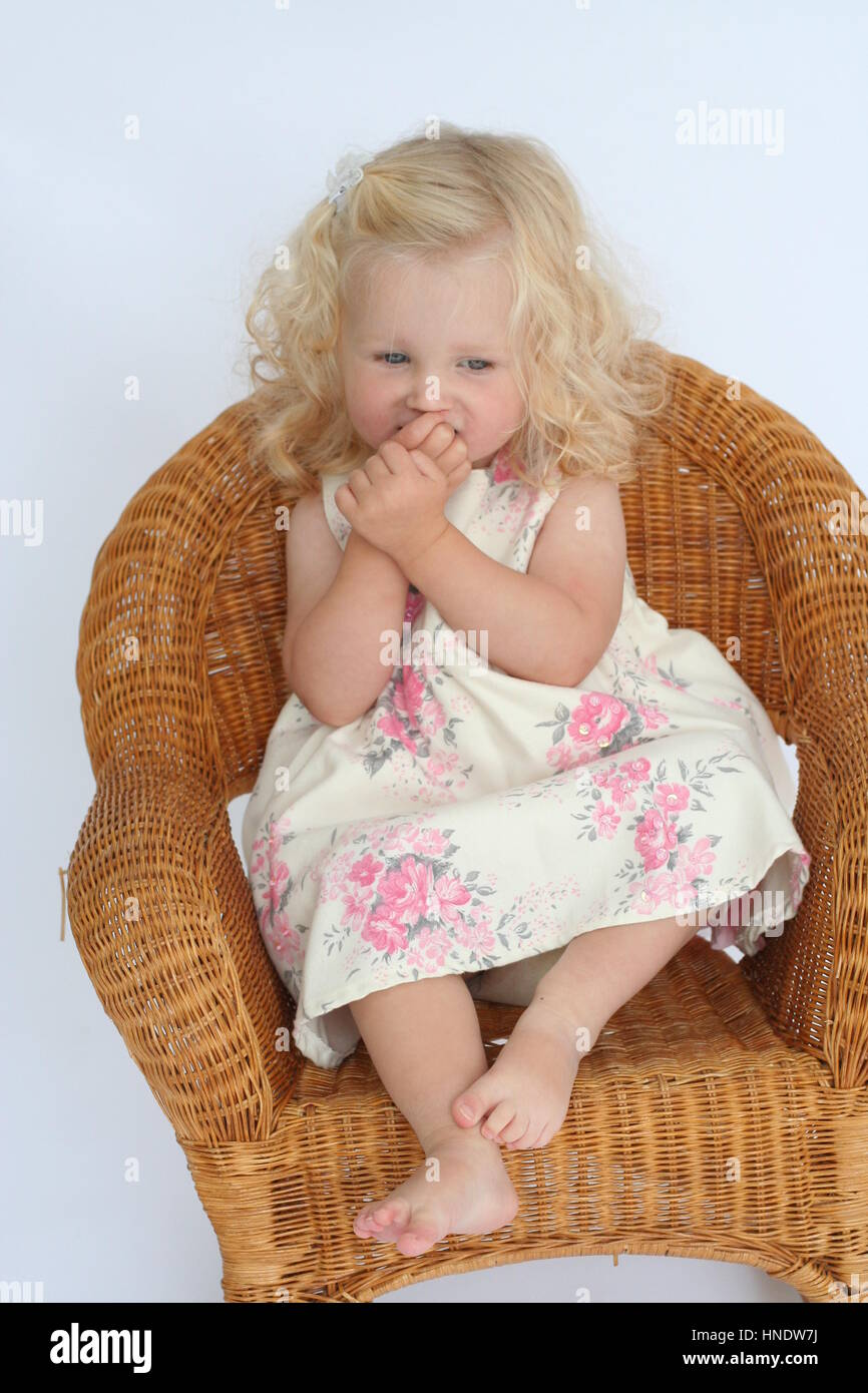Little Curly Blonde Toddler Girl Sitting In A Wicker Chair