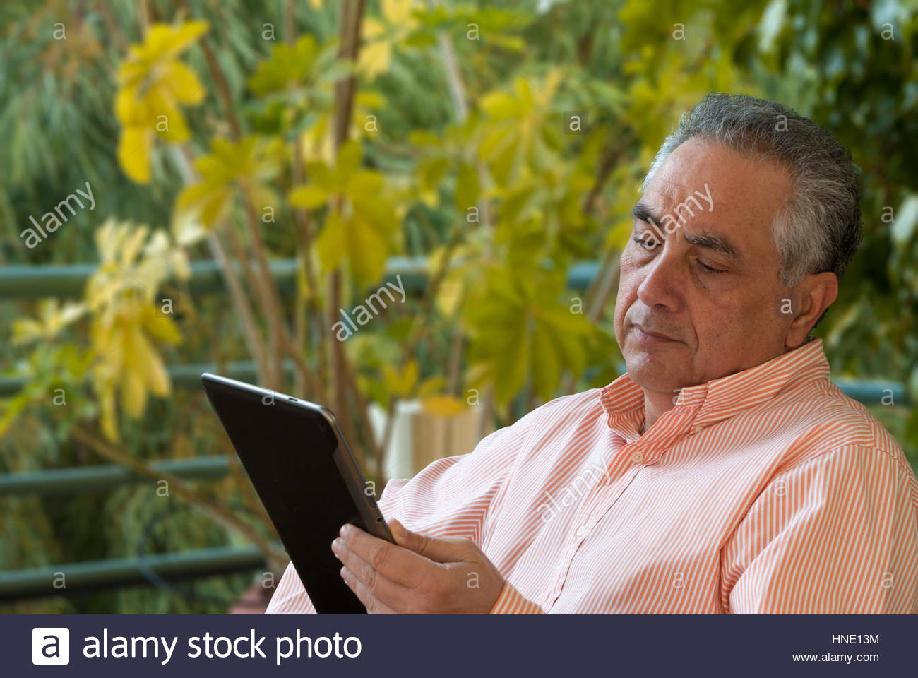 Man sitting in his balcony and reading from a tablet - Stock Image