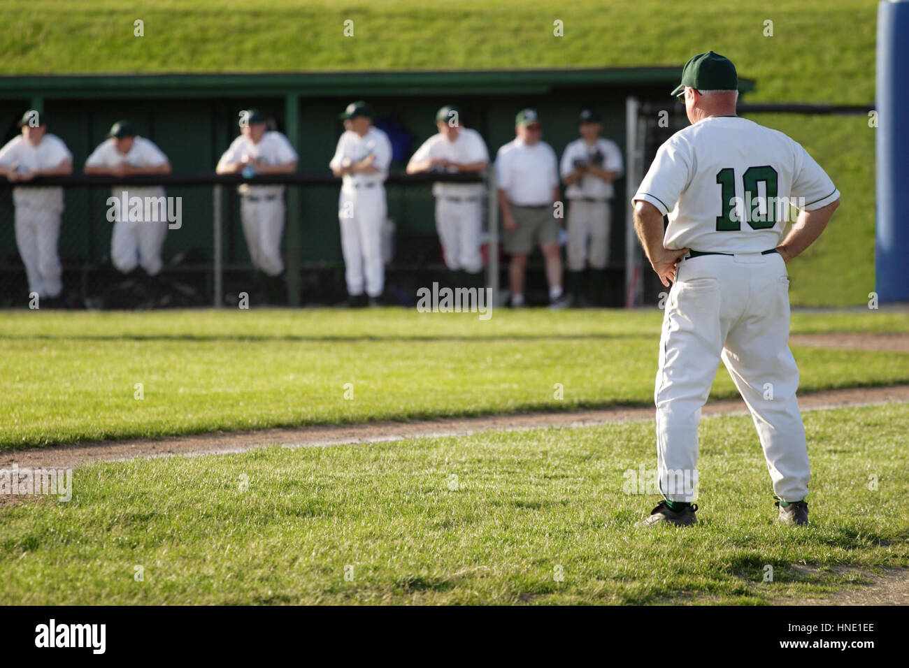 Coach looking at baseball team in dugout - Stock Image