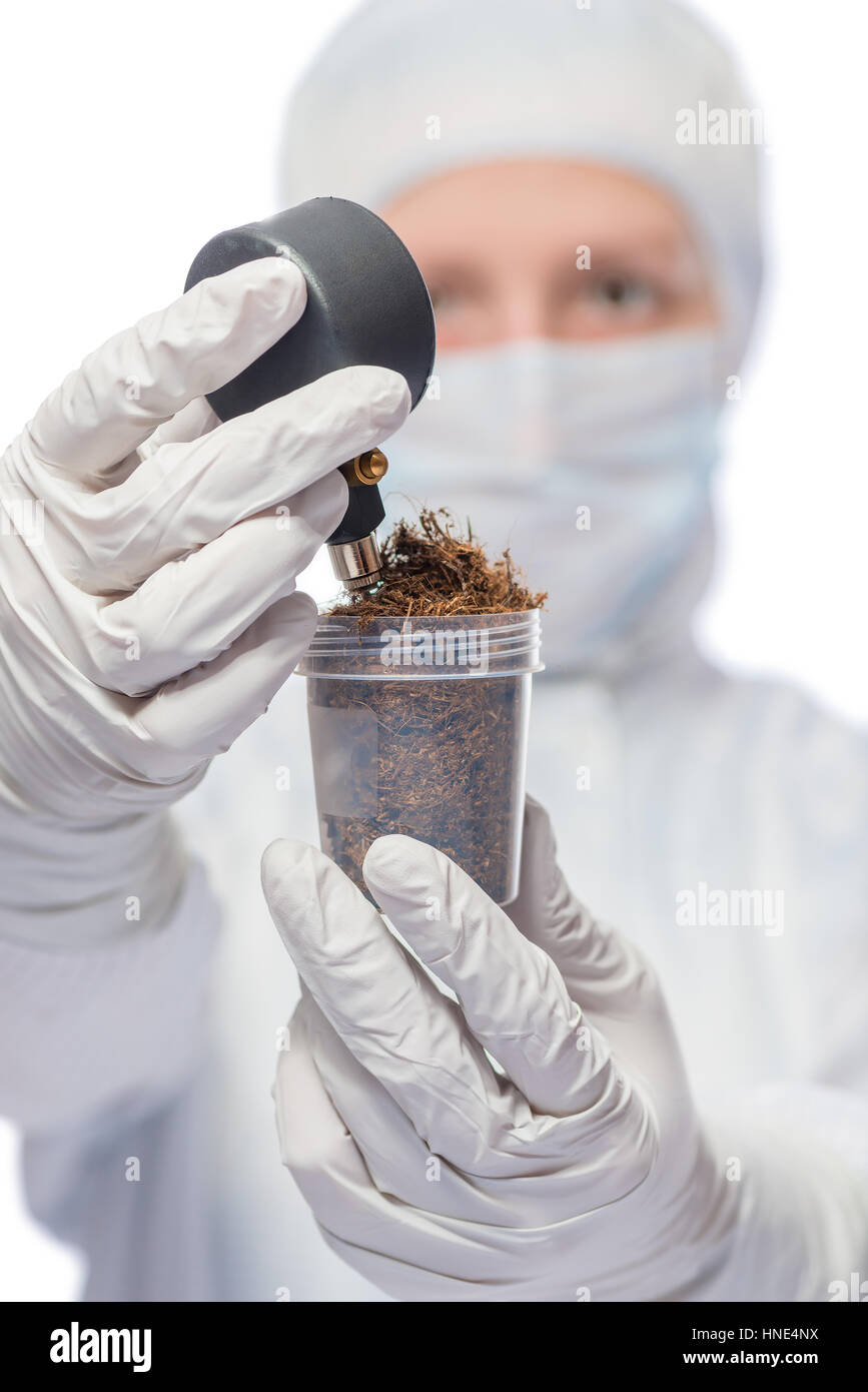 researchers measured the level of radiation in the soil sample in a protective suit - Stock Image