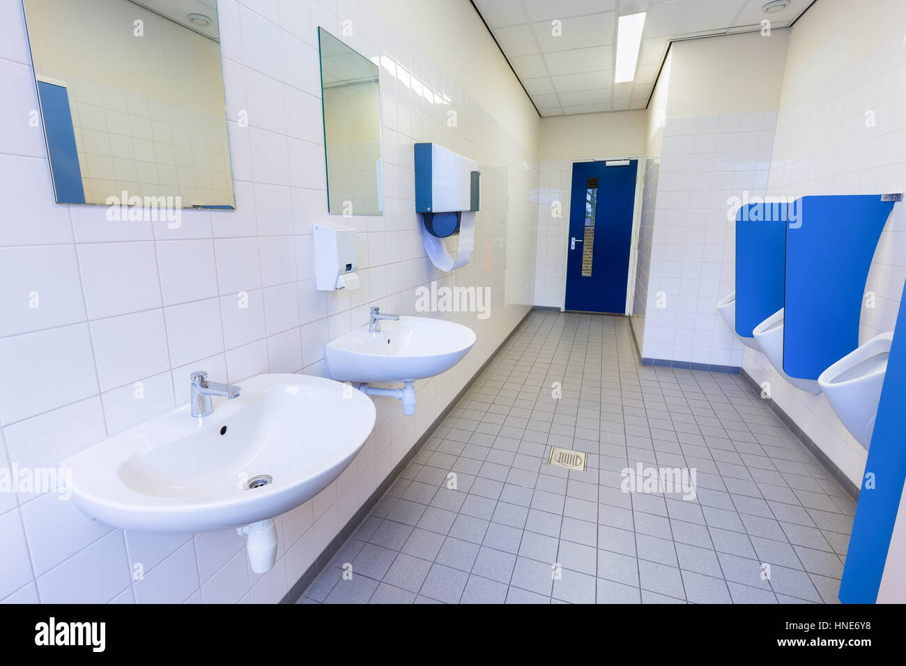Toilet room for boys with urinals sinks and mirrors on high school ...