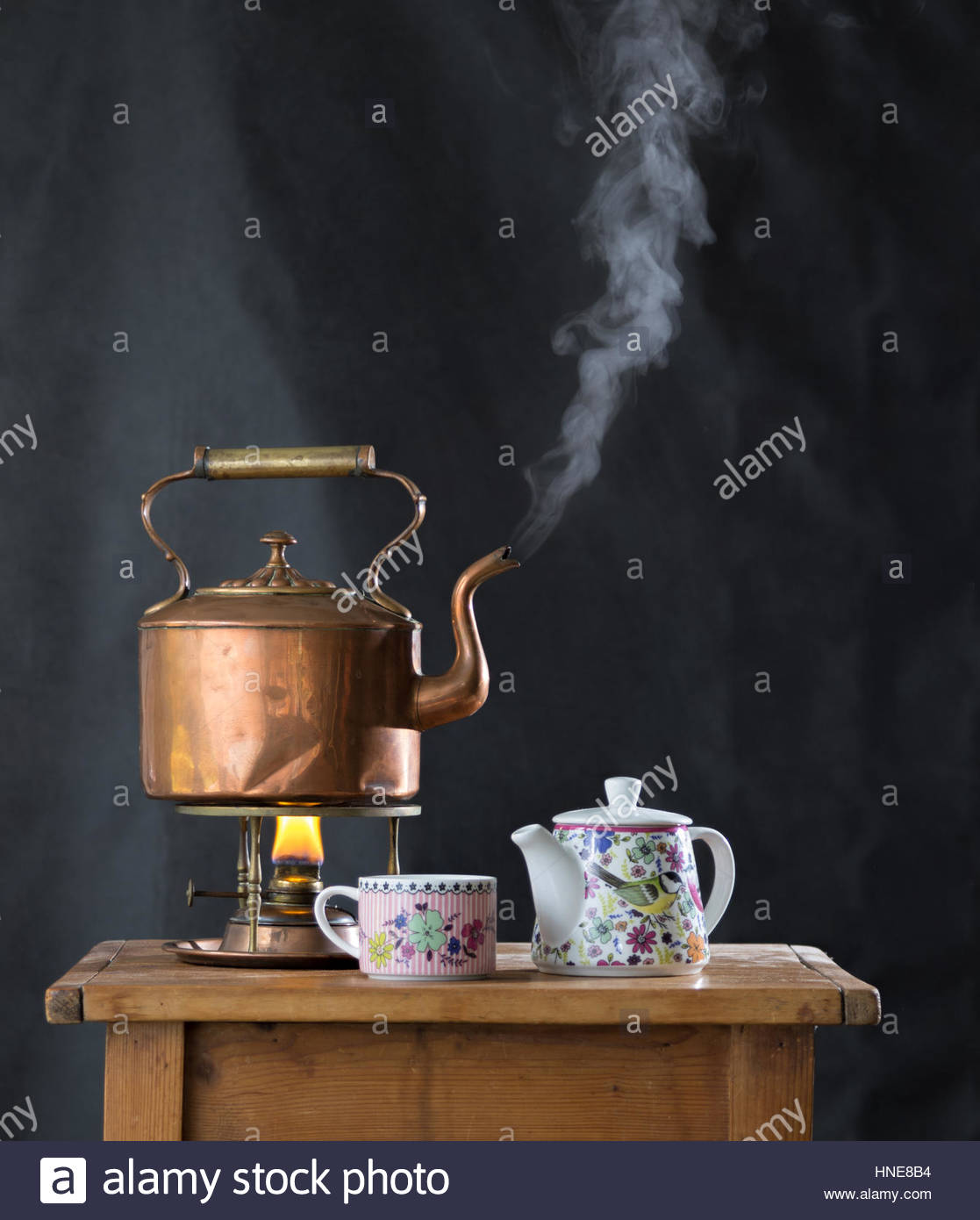 Still life with an antique boiling copper kettle, tea pot and cup - Stock Image