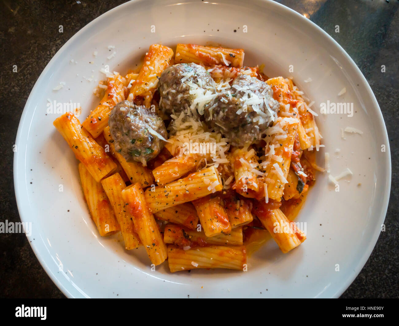 Food Ionian polpette meat balls, tomato sage and caper Ragu, short penne pasta, and pecorino cheese  served in a - Stock Image
