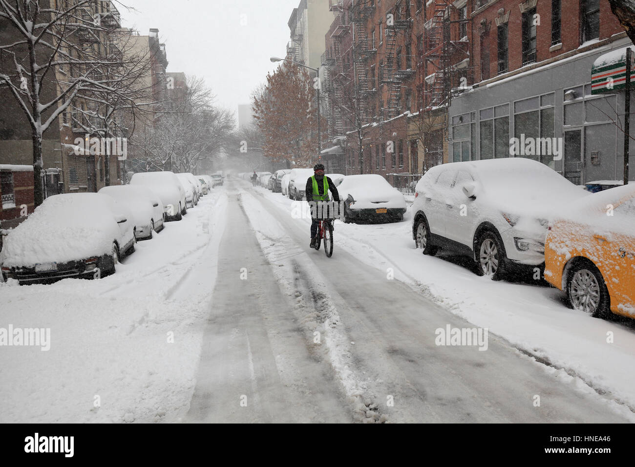 Biker in East Village, NY, during winter storm - Stock Image
