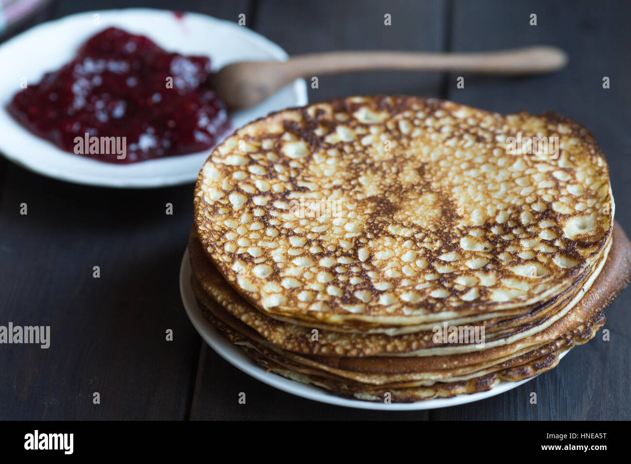 Homemade pancakes with raspberry jam on a dark wooden table. Top view with hands. Shrove Tuesday. - Stock Image