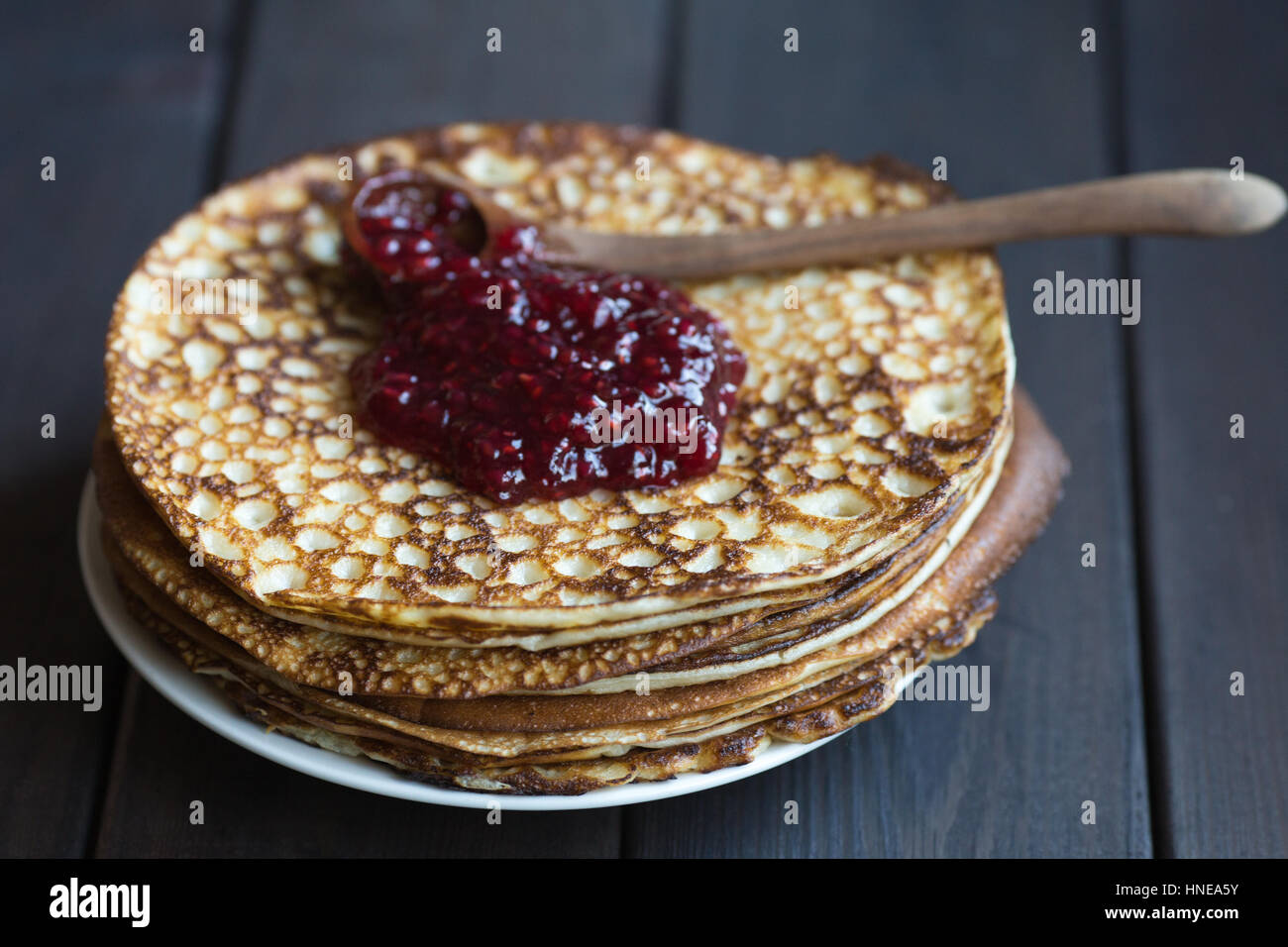 Homemade pancakes with raspberry jam on a dark wooden table. Top view with hands. Shrove Tuesday. Stock Photo