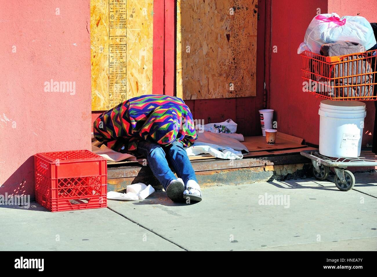 A homeless man among his belongings in a boarded up storefront entryway in Chicago's Chinatown neighborhood. - Stock Image
