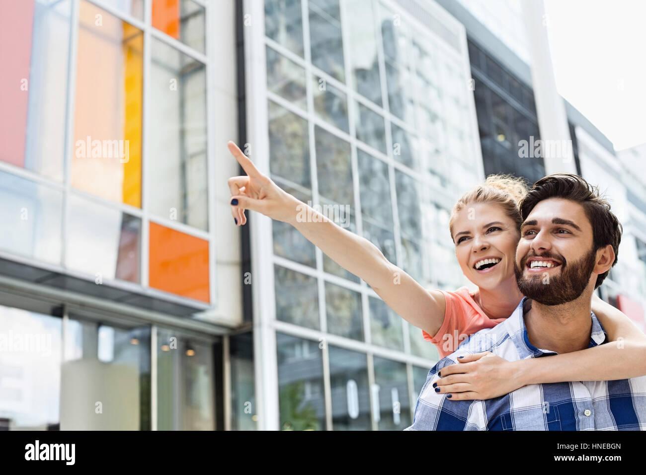 Cheerful woman showing something to man while enjoying piggyback ride in city Stock Photo