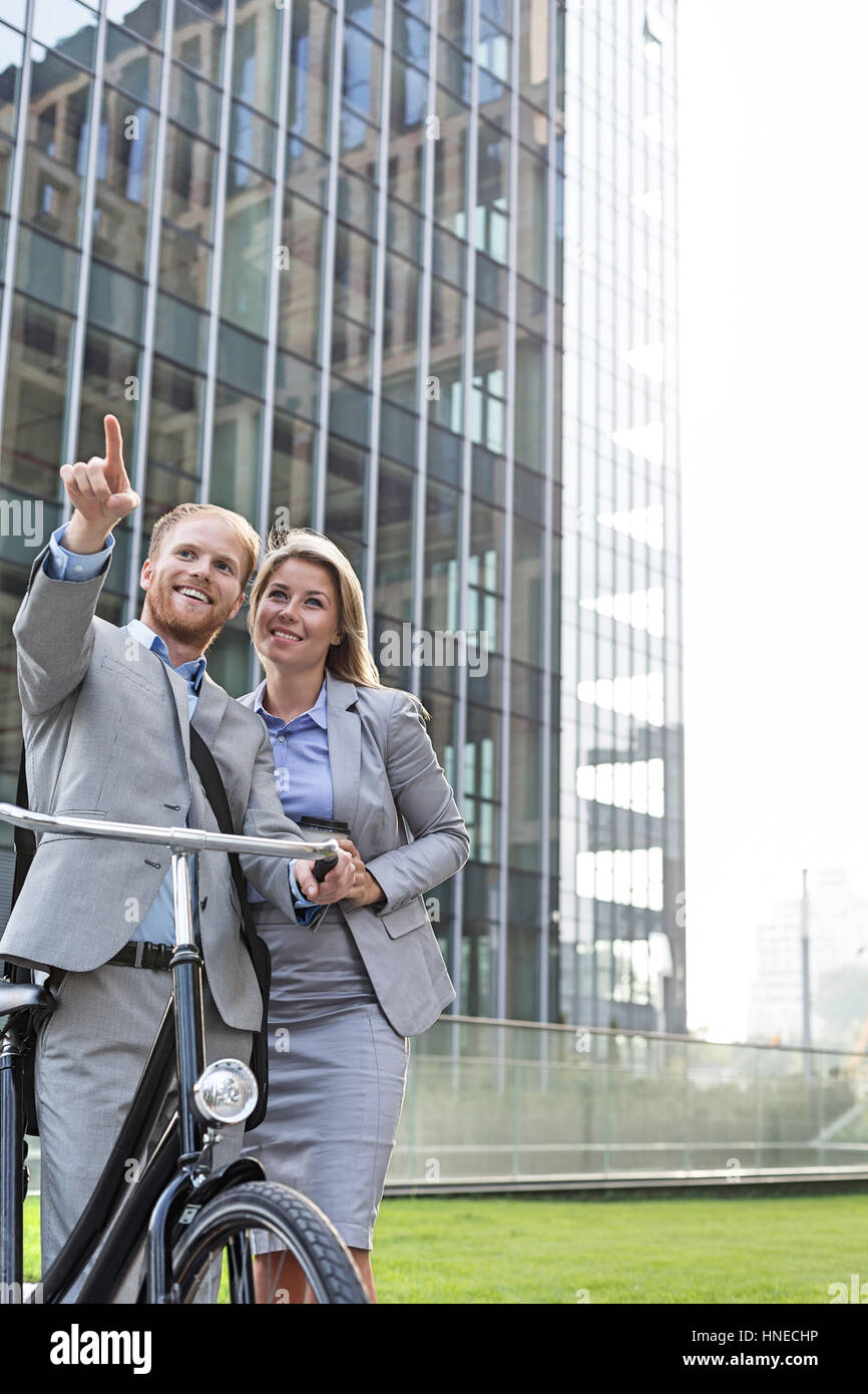 Happy businessman showing something to businesswoman in city - Stock Image