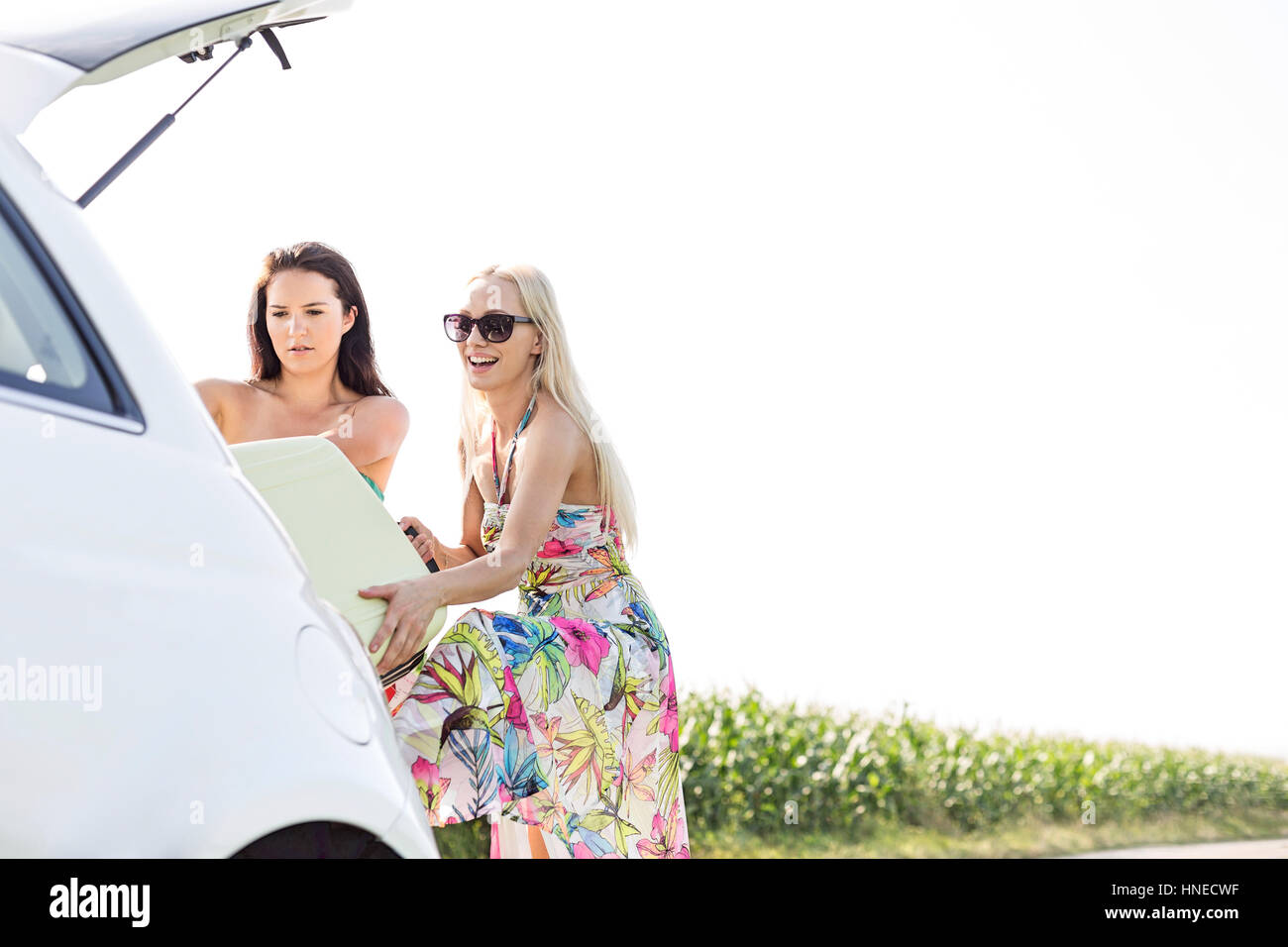 Happy female friends loading luggage in car trunk against clear sky - Stock Image