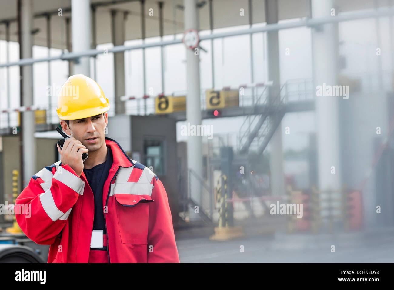 Male worker using walkie-talkie in shipping yard - Stock Image