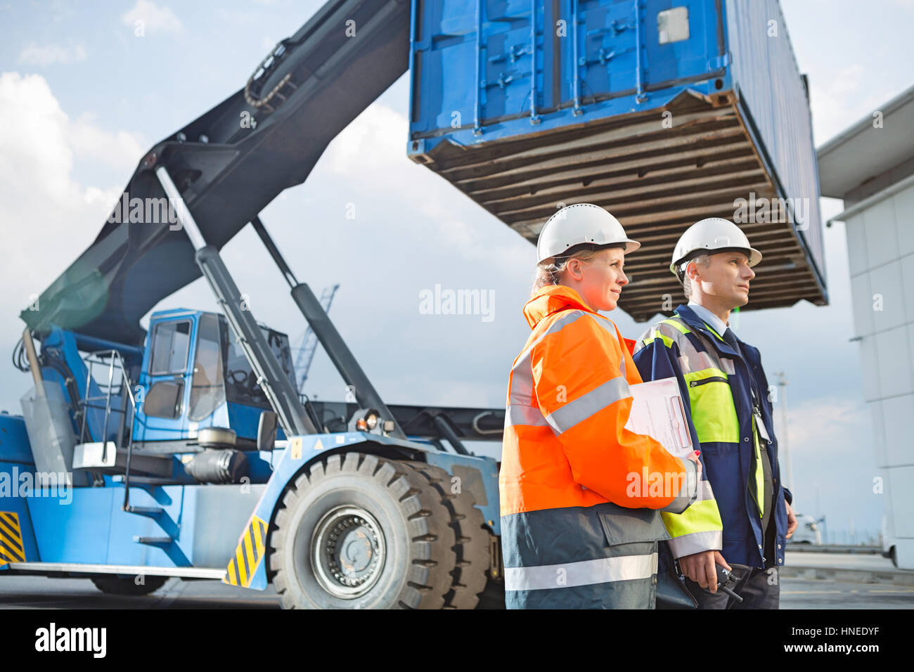 Male and female workers standing by freight vehicle in shipping yard - Stock Image