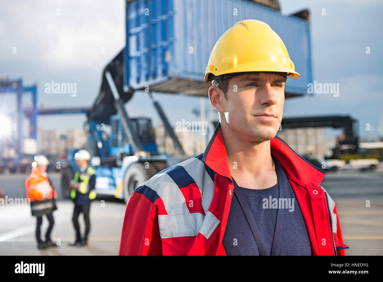Confident male worker with colleagues in background at shipping yard - Stock Image