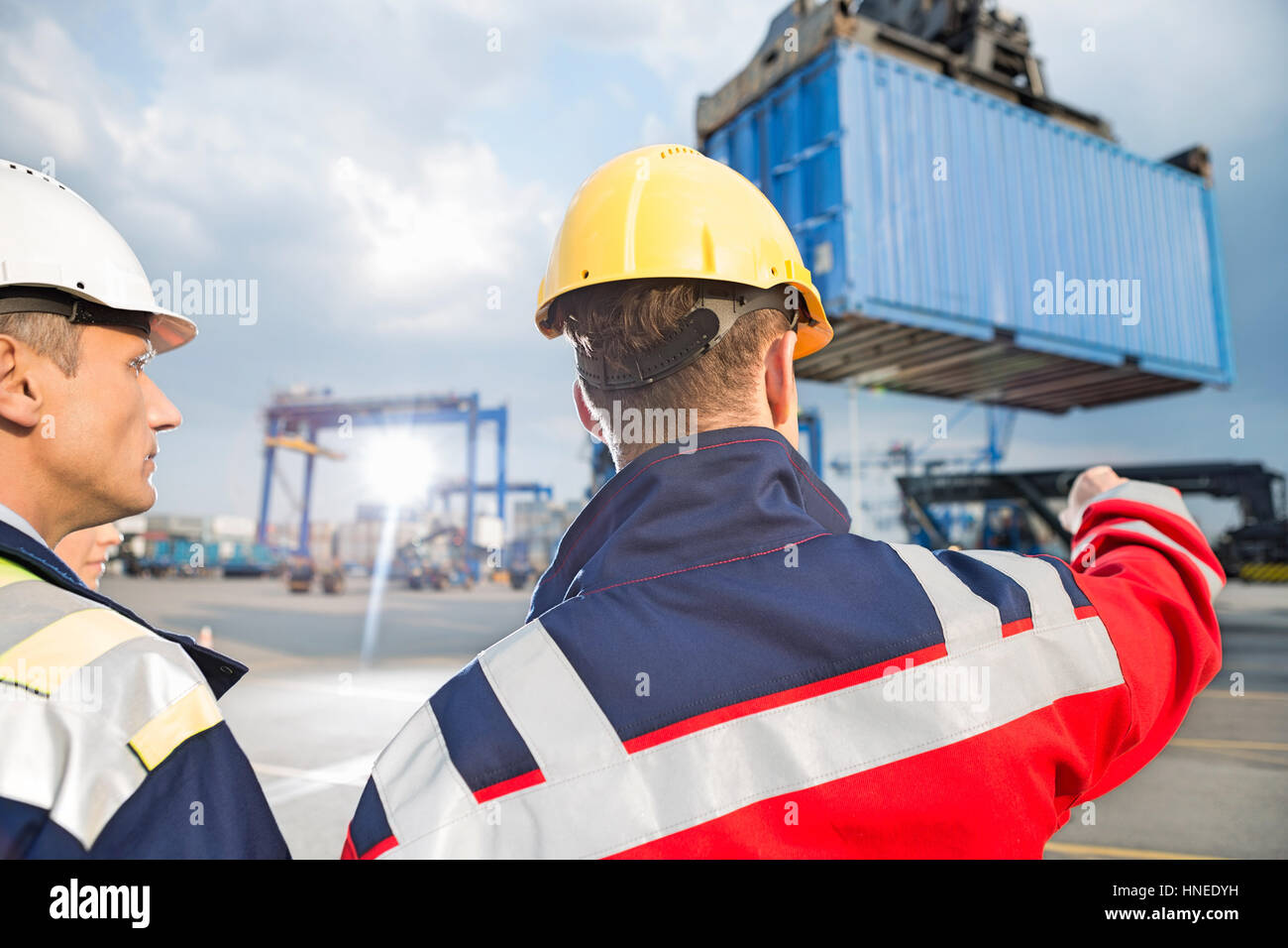 Rear view of male workers discussing in shipping yard - Stock Image