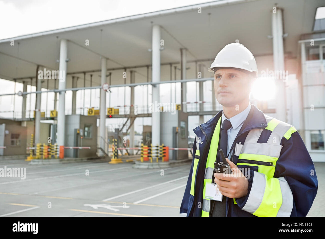 Middle-aged male worker holding walkie-talkie while looking away in shipping yard - Stock Image