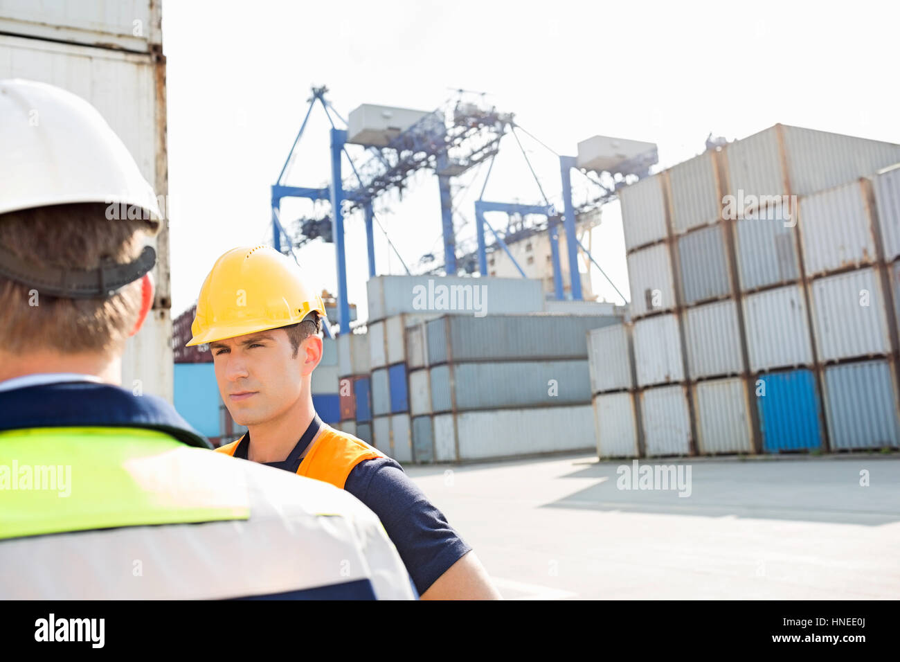 Male workers standing in shipping yard - Stock Image
