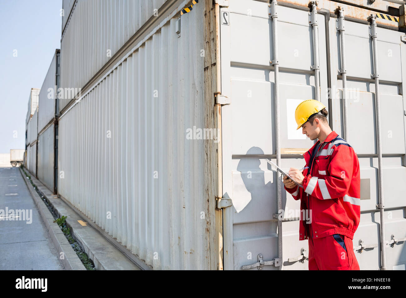 Male worker inspecting cargo container while writing on clipboard in shipping yard - Stock Image