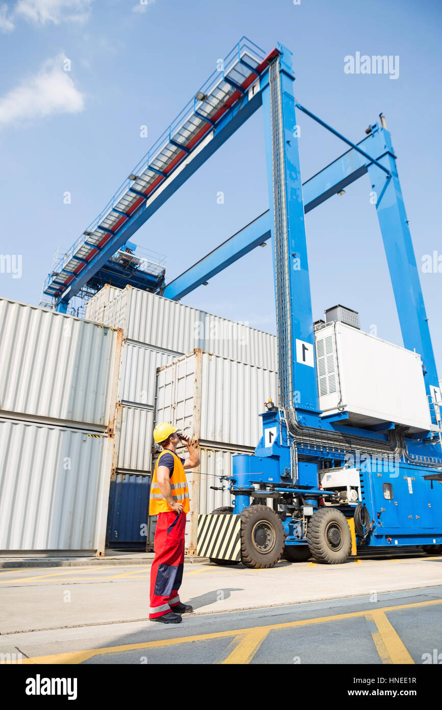 Full-length of worker using walkie-talkie in shipping yard - Stock Image