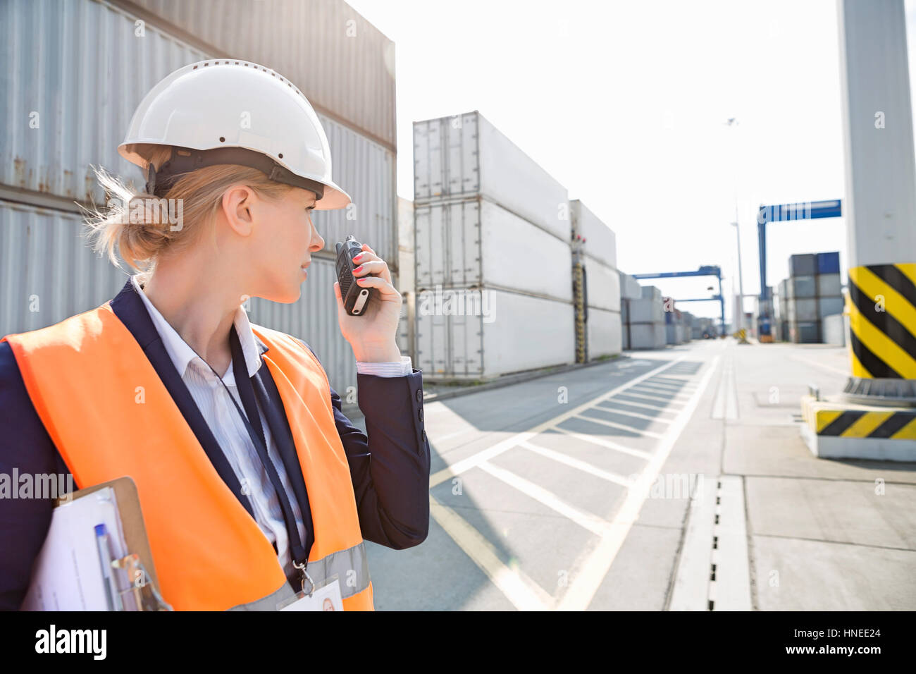 Female engineer using walkie-talkie in shipping yard - Stock Image