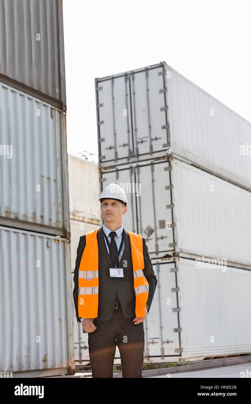 Middle-aged man standing against cargo containers in shipping yard - Stock Image