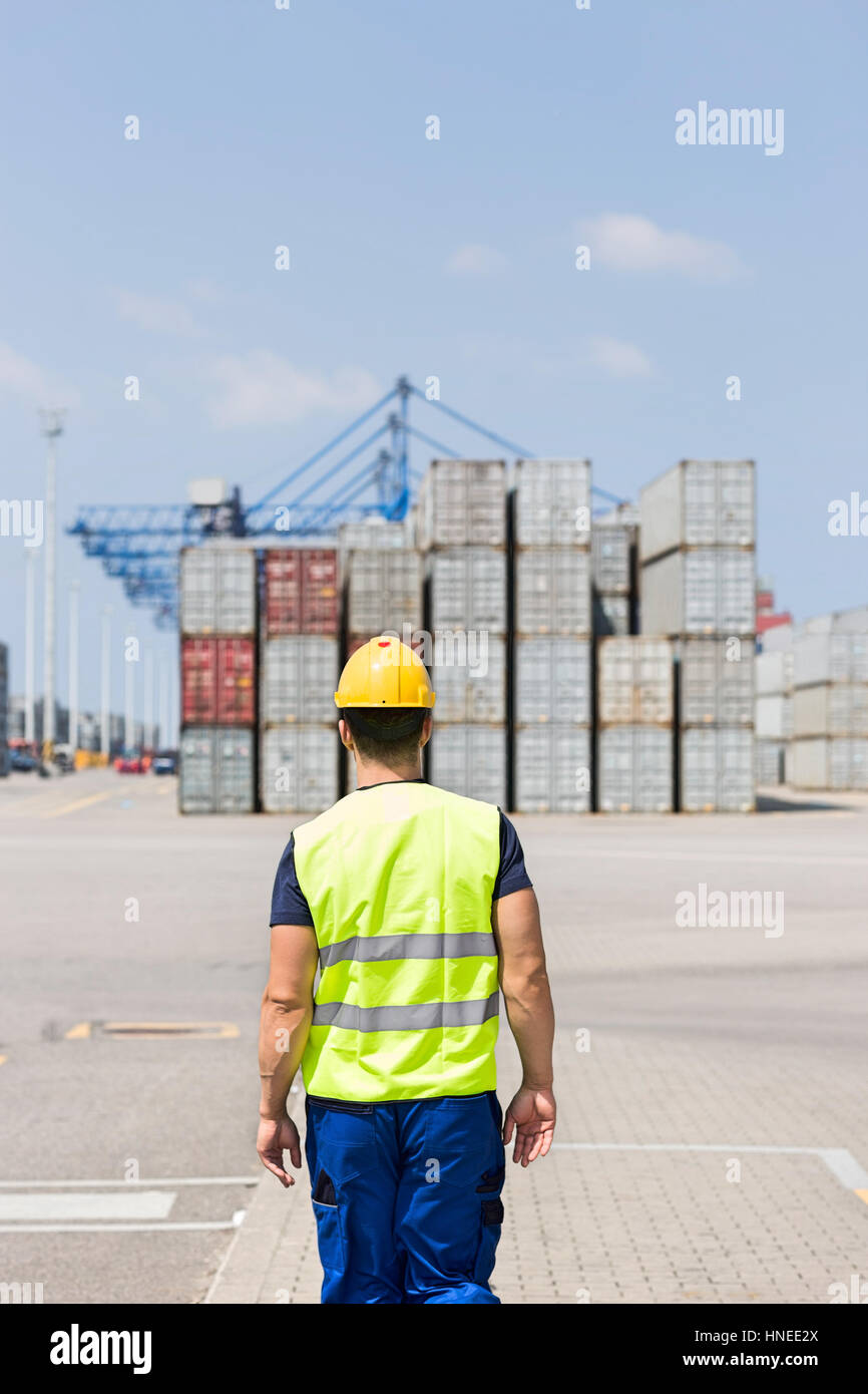 Rear view of mid adult worker walking in shipping yard Stock Photo