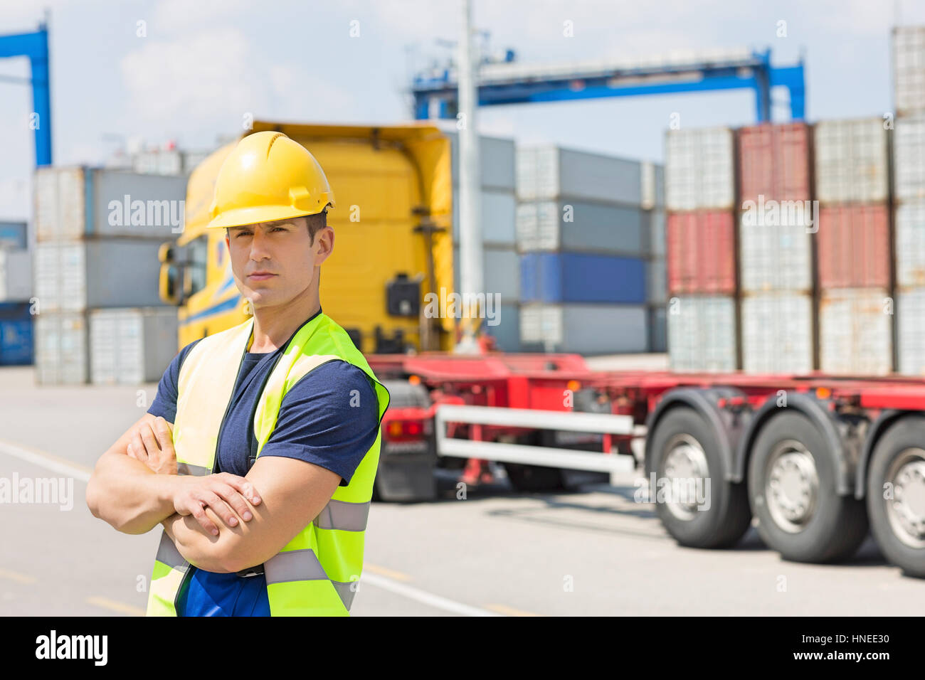 Portrait of confident mid adult man in shipping yard - Stock Image