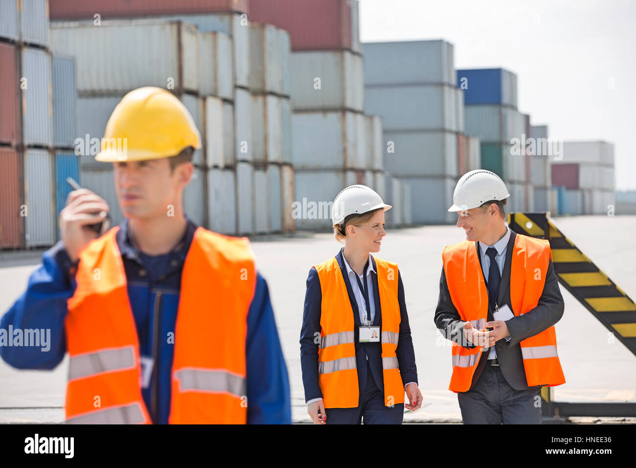 Worker using walkie-talkie while colleagues discussing in shipping yard - Stock Image