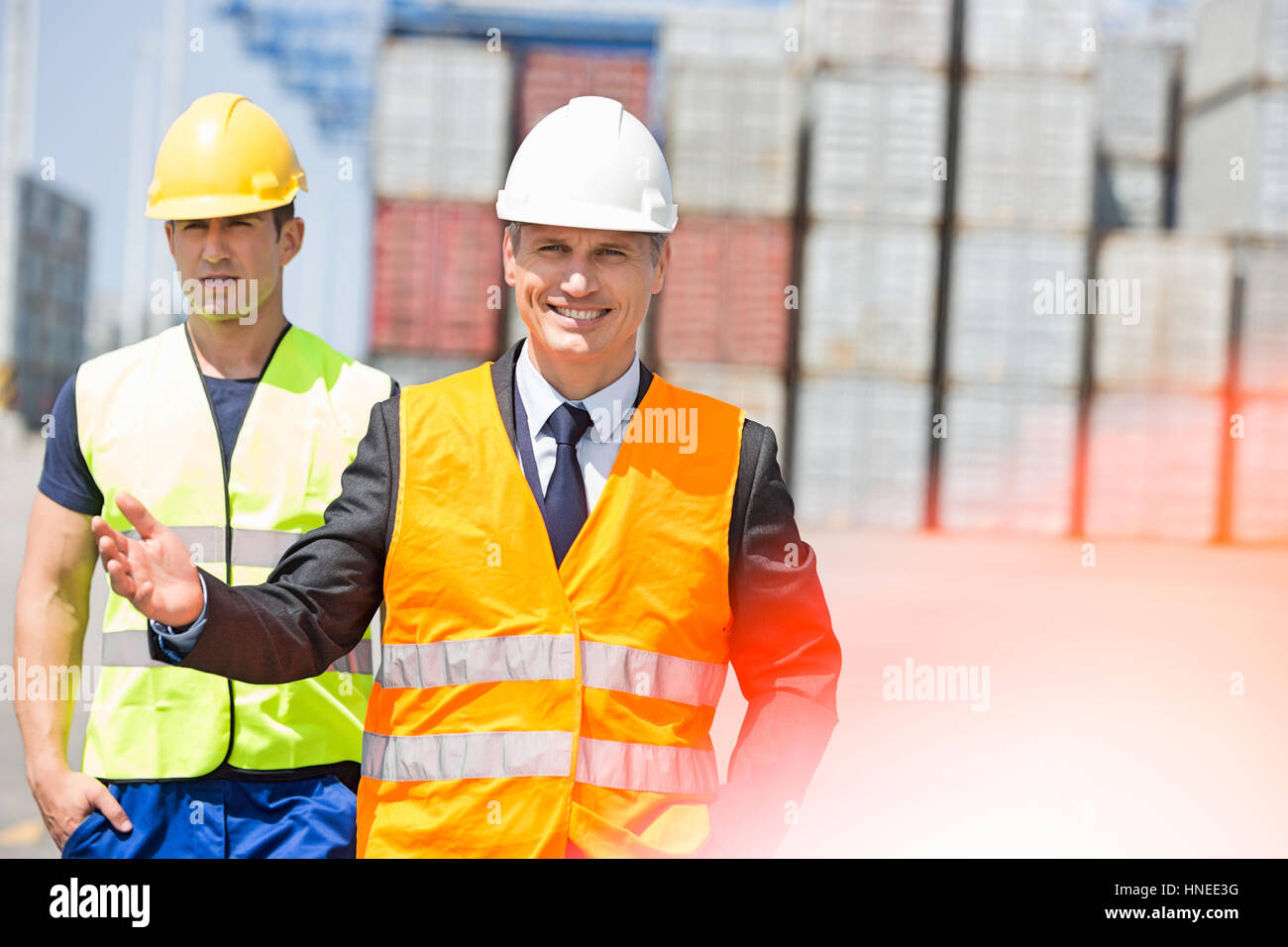 Male workers walking in shipping yard - Stock Image