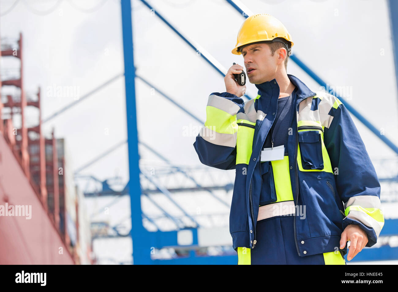 Mid adult male worker using walkie-talkie in shipping yard - Stock Image