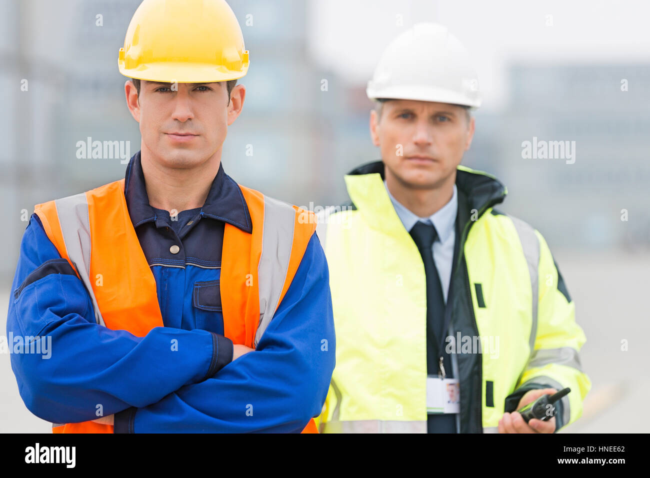 Portrait of confident worker standing with coworker in shipping yard - Stock Image