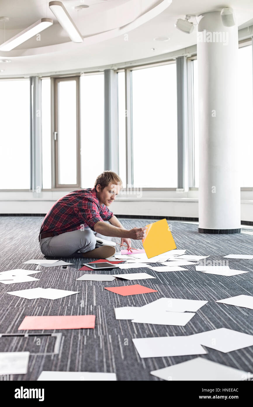 Businessman organizing photographs while sitting on floor at creative office - Stock Image