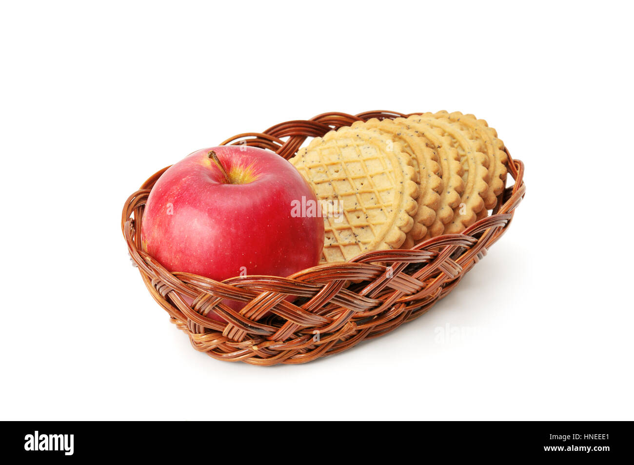 apples and biscuit in basket isolated on a white - Stock Image