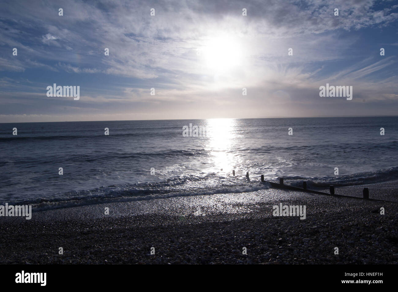 Seascape of sun casting a reflection over a dark-blue sea, with a blue sky above partially covered by wispy clouds - Stock Image