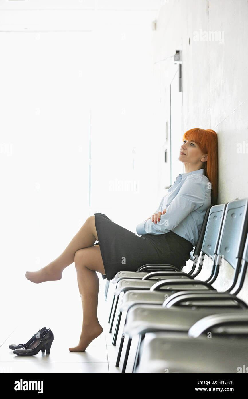 Thoughtful businesswoman sitting with legs crossed on chair in office - Stock Image