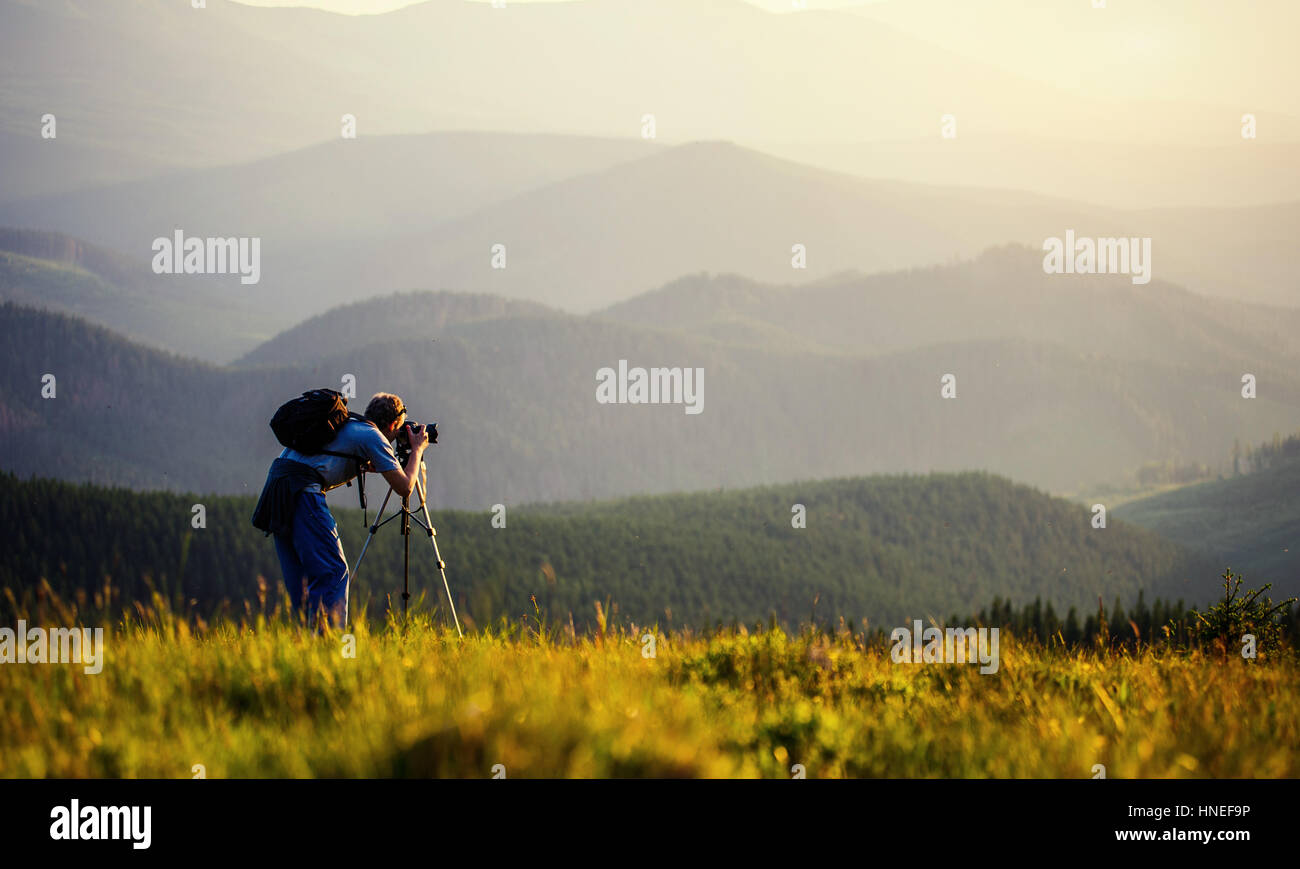 photographer photographed mountains in summer, photographs fog - Stock Image