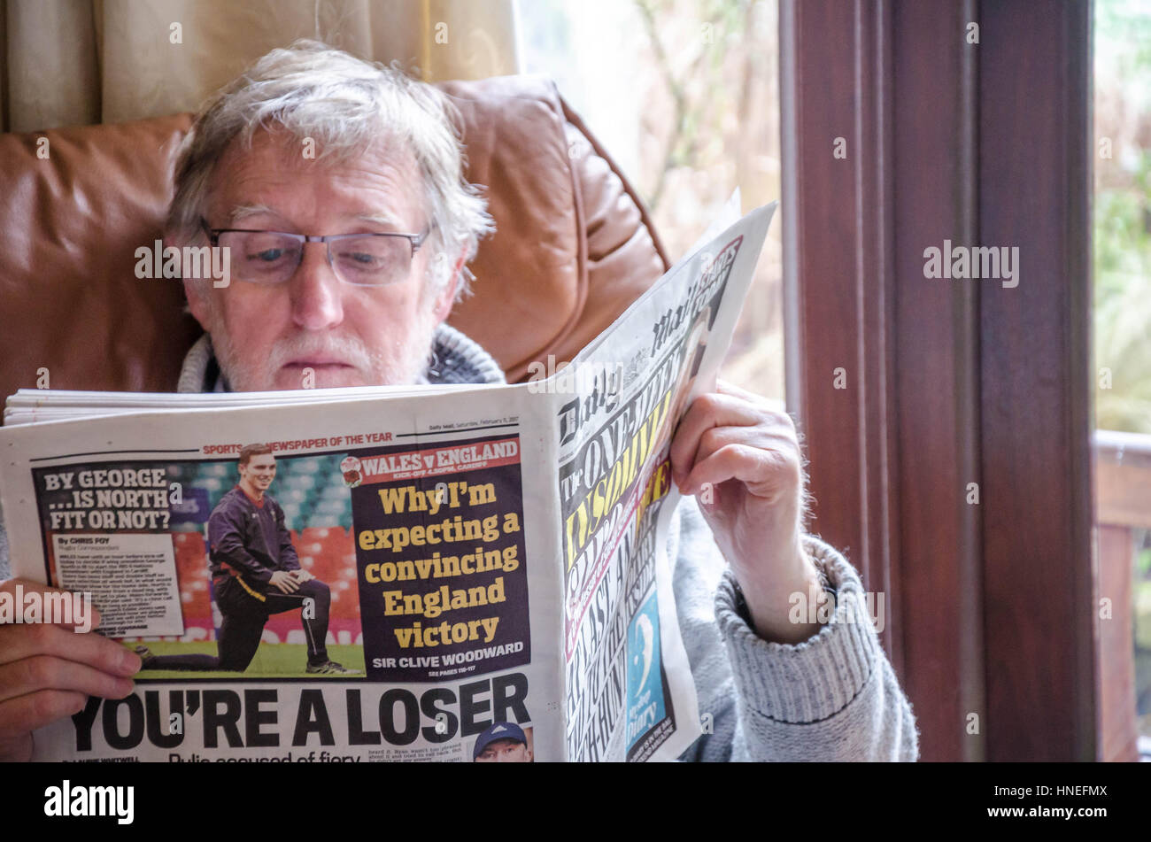 A man sits in Ann armchair reading the Daily Mail newspaper - Stock Image