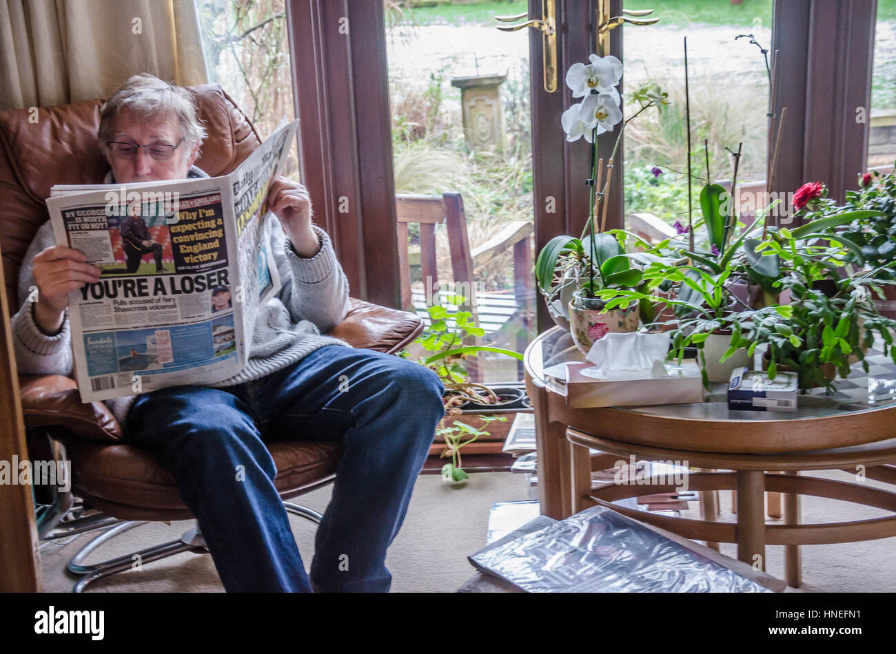 a man sits in a fy armchair reading the daily mail newspaper HNEFN1