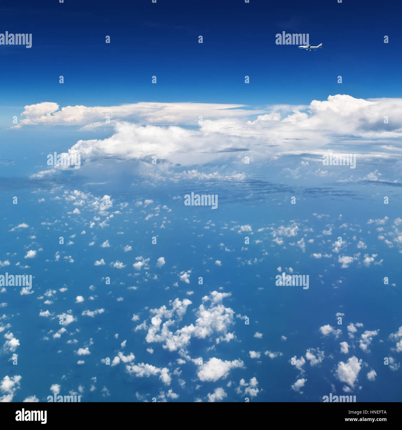 Oncoming flight traffic in mid air. Aircraft flying above ocean, beautiful white cloud. Clear blue sky, aerial view Stock Photo