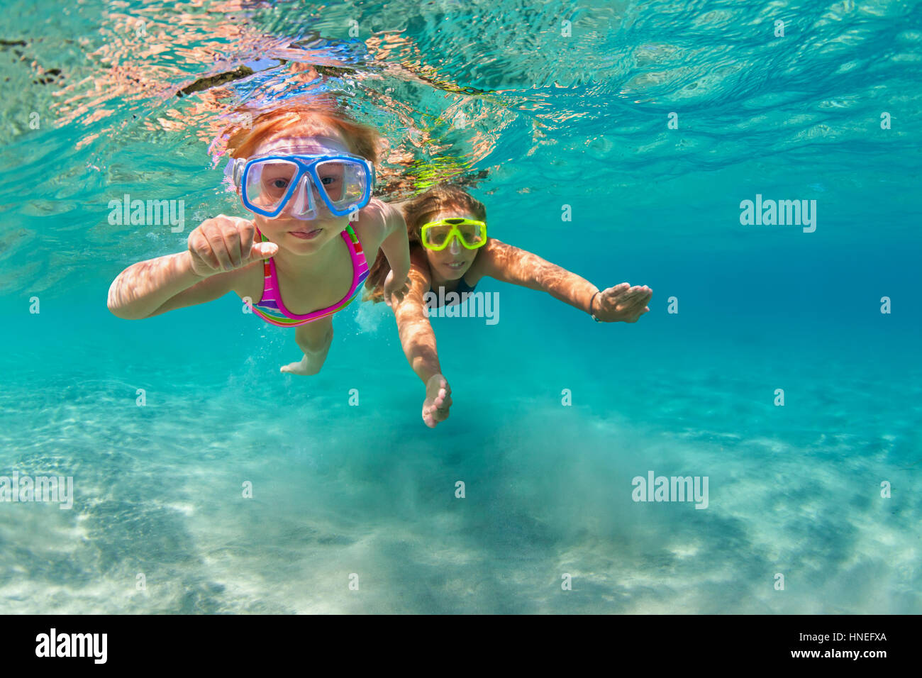 Happy family - mother with baby girl dive, swim underwater with fun in sea pool. Lifestyle, active parent, people - Stock Image