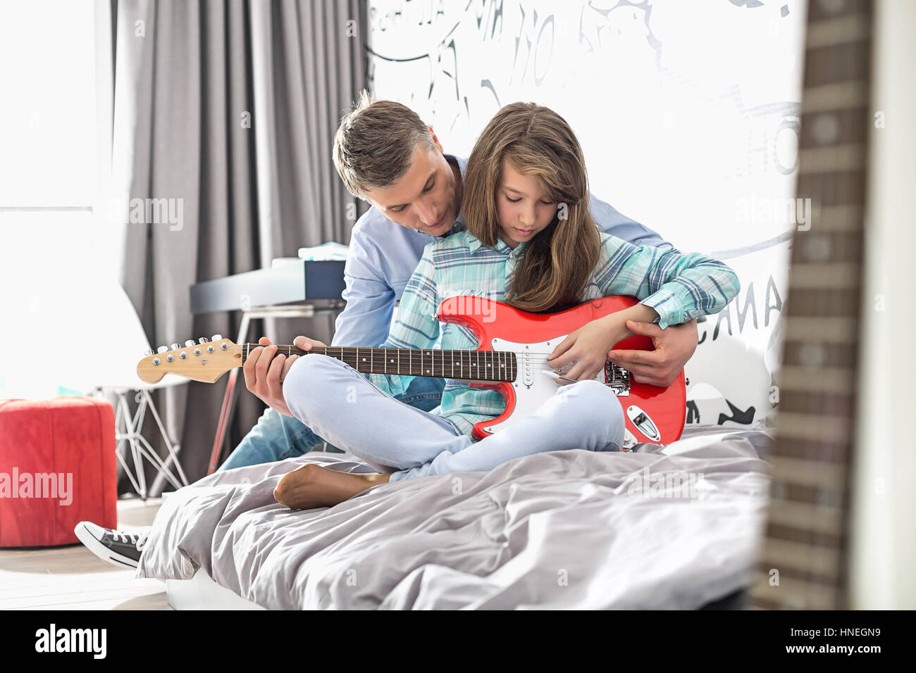 Father teaching daughter to play guitar at home - Stock Image