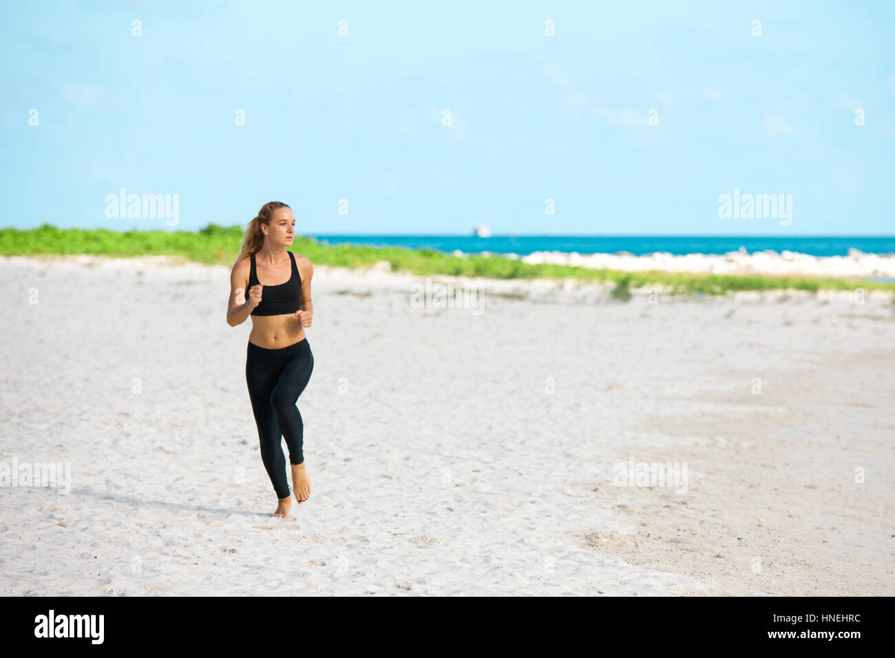 young fitness woman running at beach - Stock Image